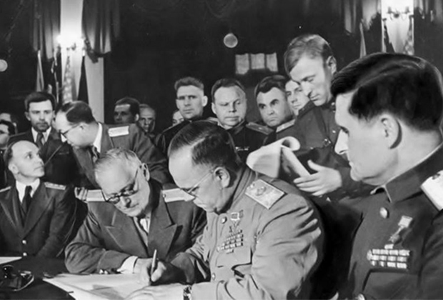 May 8, 1945. Karlshorst, Berlin. Marshal Georgy Zhukov signs the German Surrender Act. Colonel of the NKVD Alexander Korotkov stands behind Zhukov